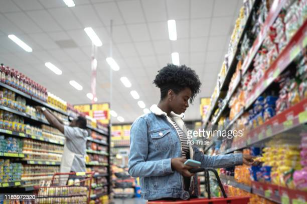 young woman choosing products in supermarket - market retail space stock pictures, royalty-free photos & images