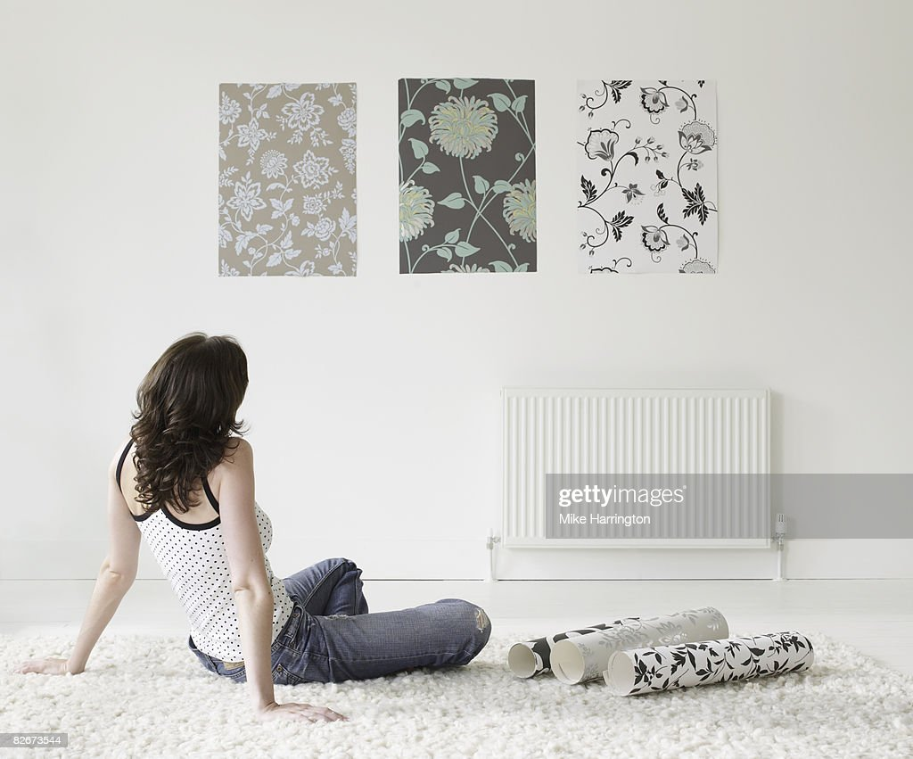 Young woman choosing wall paper for home : Stockfoto