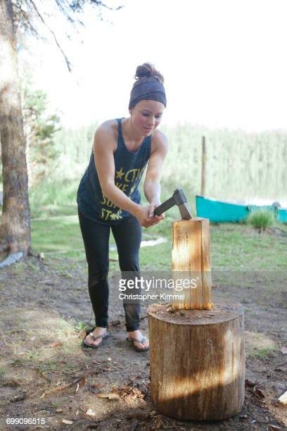 A young woman chops firewood with a small axe while camping at Unna Lake in Bowron Lake Provincial Park