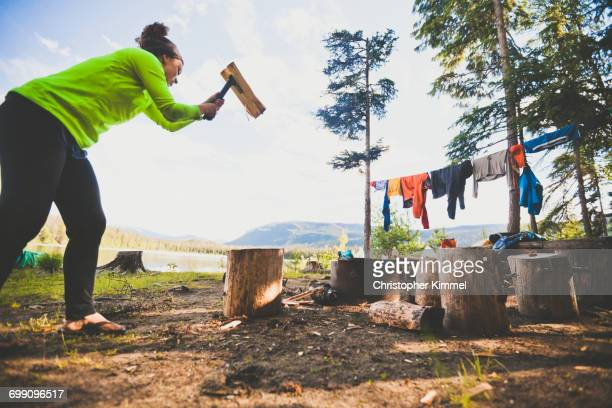 A young woman chops firewood with a small axe while camping at Unna Lake in Bowron Lake Provincial Park.