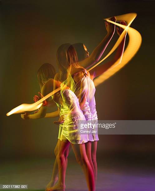 Young woman circled by trail of light (multiple exposure)