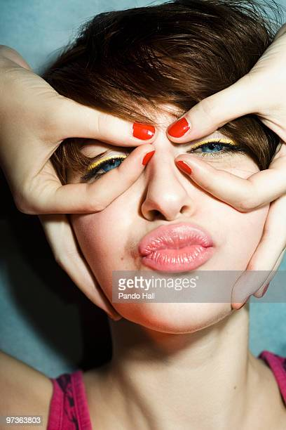 Young woman circling eyes with fingers