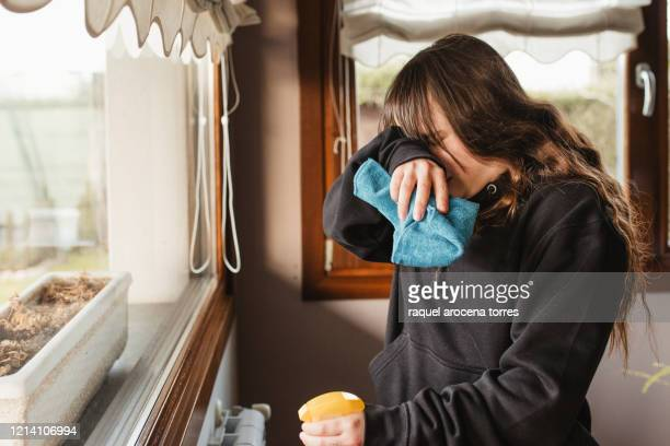 young woman cleaning a house and suffering from spring allergy - mucus stock pictures, royalty-free photos & images