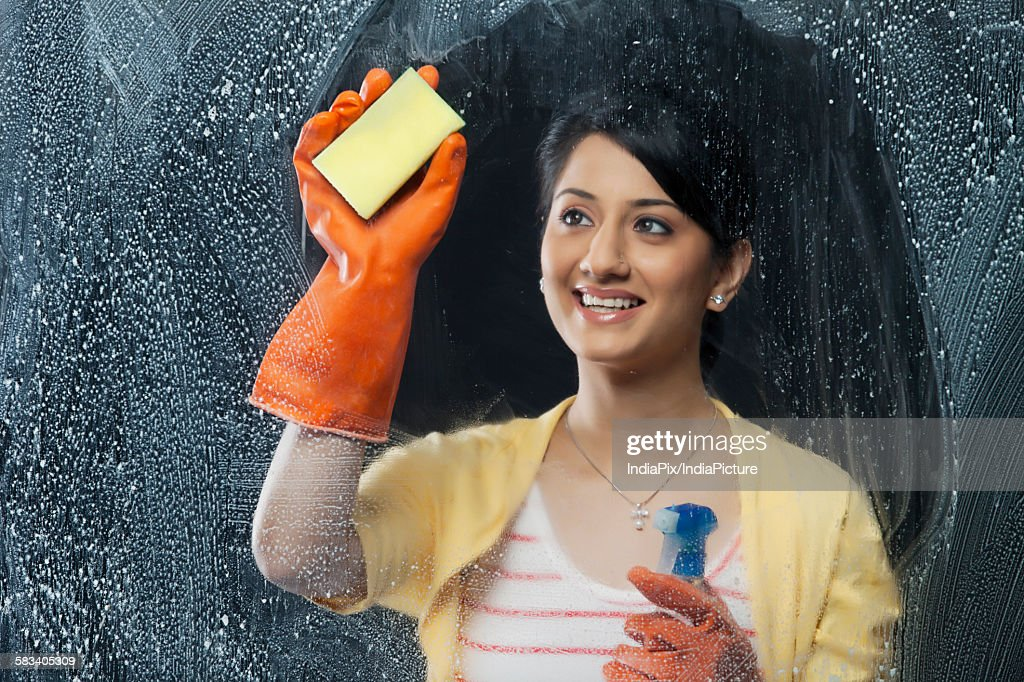 Young woman cleaning a window : Stock Photo