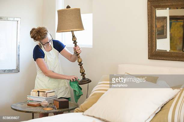 young woman cleaning bedroom with green cleaning products - heshphoto stock pictures, royalty-free photos & images