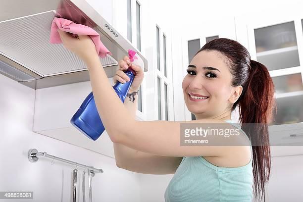 young woman cleaning cooker hood - afzuigapparaat stockfoto's en -beelden