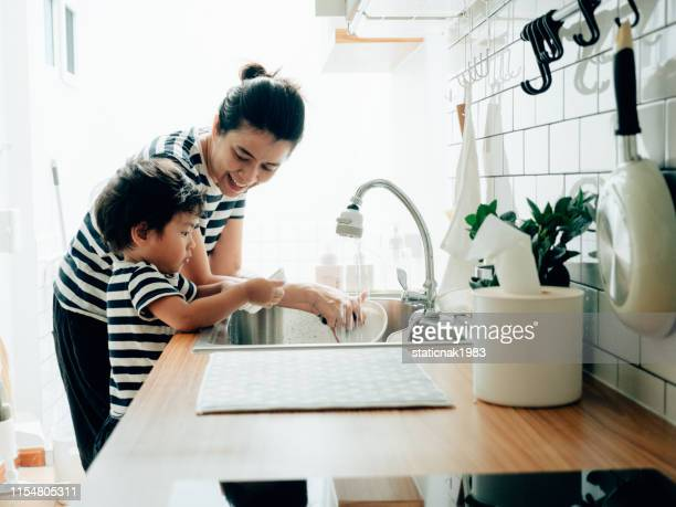 young woman cleaning dishes with her son at home. - washing up stock pictures, royalty-free photos & images
