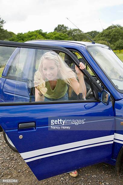 Young woman cleaning electric car