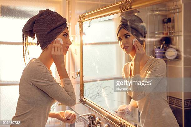 Young woman cleaning her face in the bathroom.