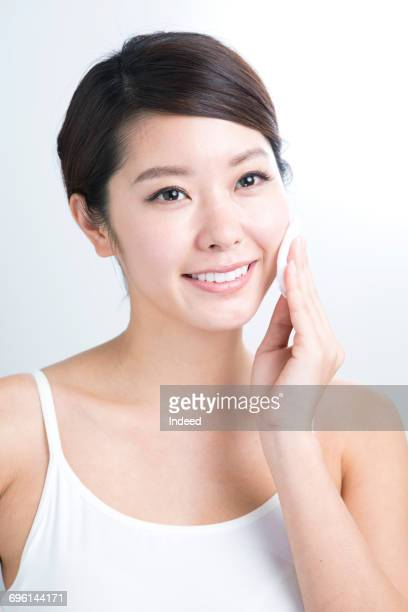 Young woman cleaning her face with cotton pad