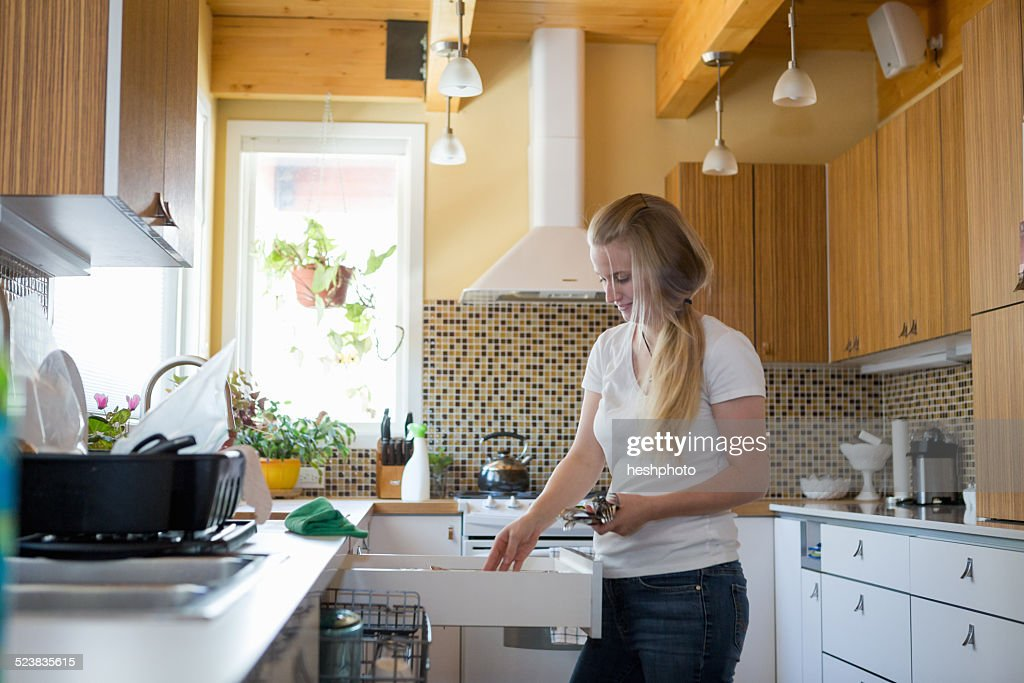 Young woman cleaning kitchen with green cleaning products : Stock Photo