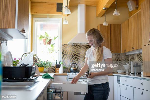 Young woman cleaning kitchen with green cleaning products