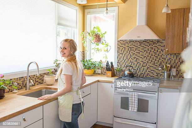 young woman cleaning kitchen with green cleaning products - heshphoto stock-fotos und bilder