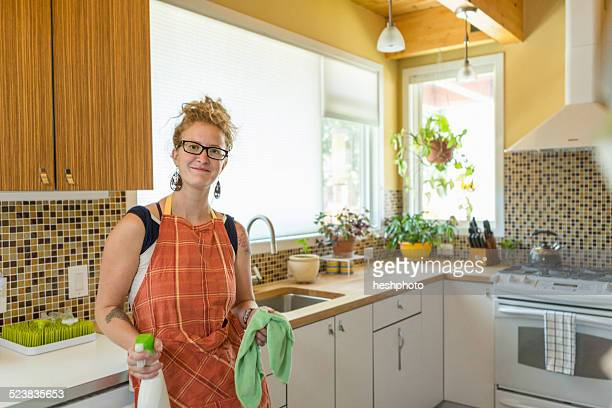 young woman cleaning kitchen with green cleaning products - heshphoto stock pictures, royalty-free photos & images