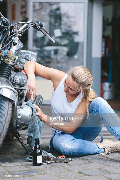 Young woman cleaning motorbike