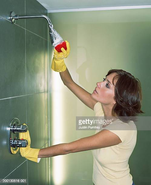 Young woman cleaning shower head