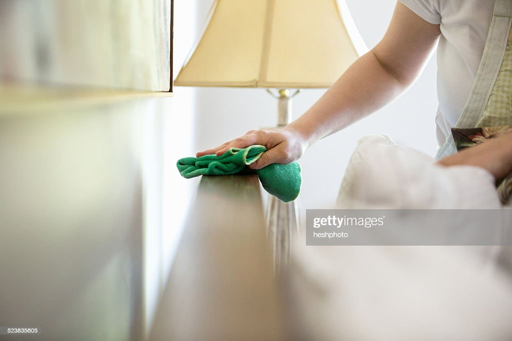 Young woman cleaning surfaces with green cleaning products : Stock Photo