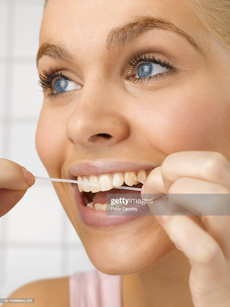 Young woman cleaning teeth with dental floss, close up, studio shot : Stock Photo