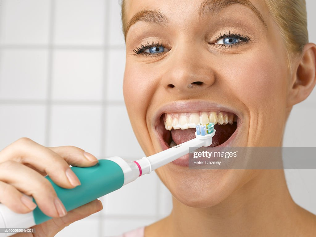 Young woman cleaning teeth with electric toothbrush, close up, studio shot : Stock Photo