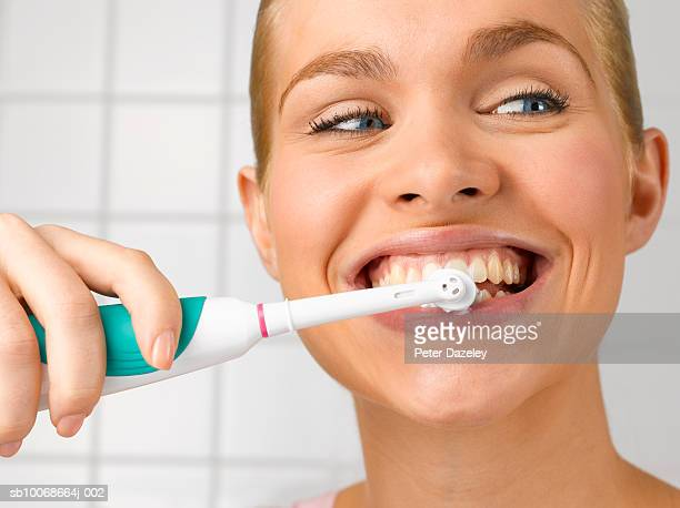 Young woman cleaning teeth with electric toothbrush, close up, studio shot