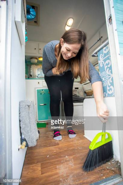 Young woman cleaning the floor of her RV