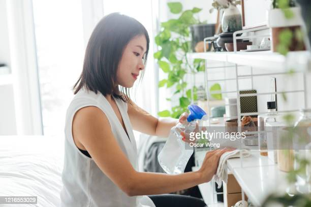 a young woman cleaning the shelving unit with sanitising spray and cloth at home during the day - cleaning agent stock pictures, royalty-free photos & images