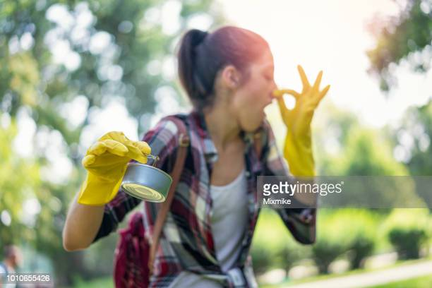 Young woman cleaning up smelly garbage in the park