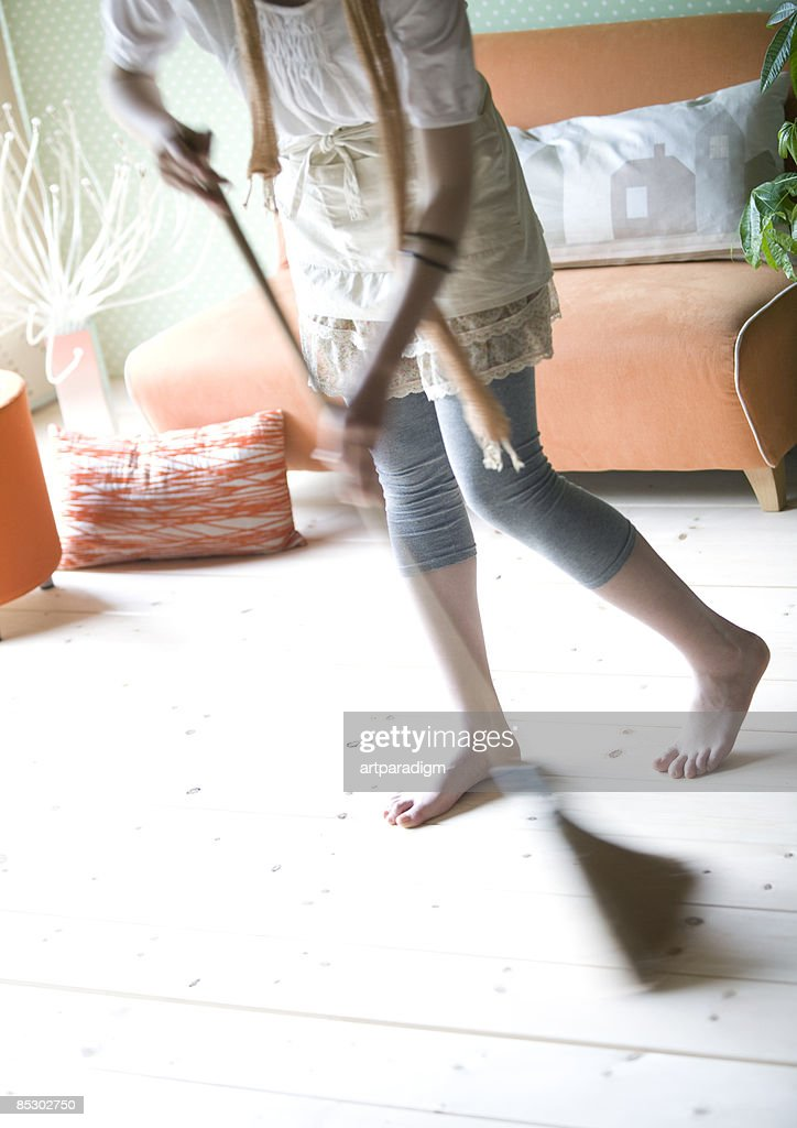Young woman cleaning up the room : Stock Photo