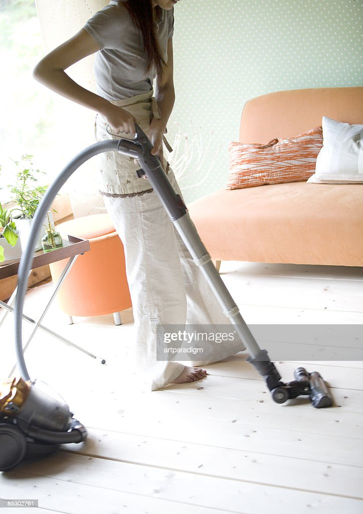 Young woman cleaning up the room : Bildbanksbilder