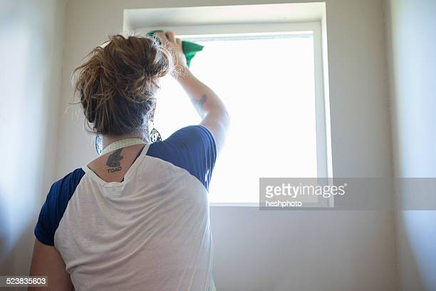 young woman cleaning window with green cleaning products - heshphoto fotografías e imágenes de stock