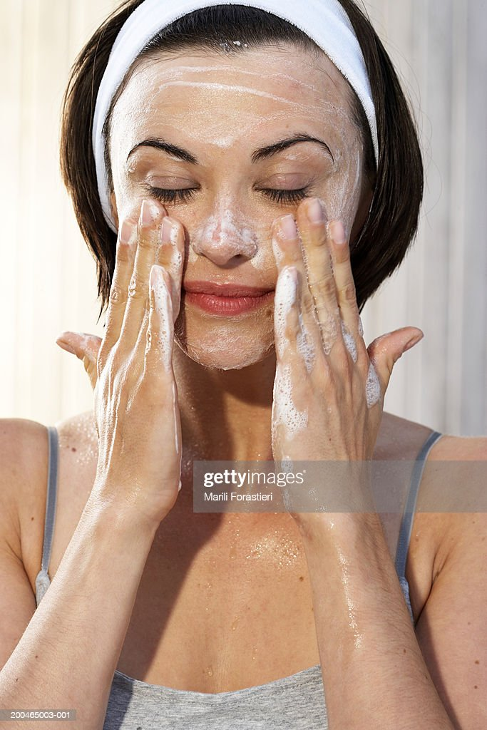 Young woman cleansing face,  close-up : Stock Photo