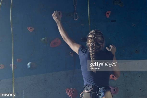 Young woman climber at the top of climbing wall