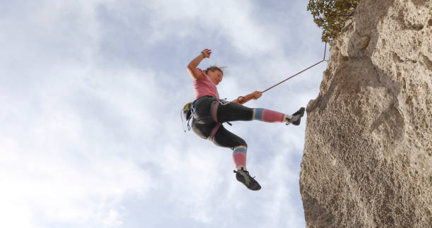 Young woman climber jumps out from rock face on the end of a rope