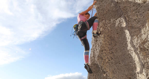 Young woman climber scales steep rock wall with a rope
