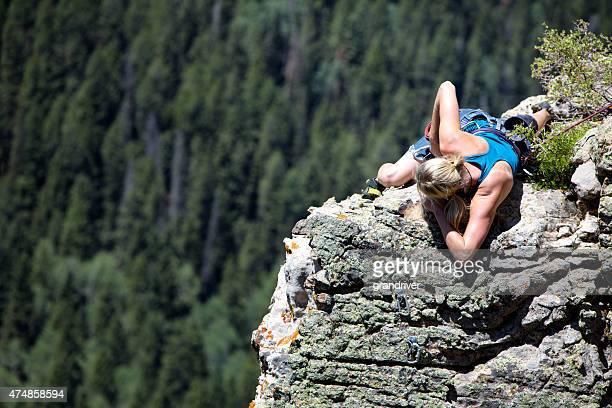Young woman Climbing a Granite Cliff  Near Moab Utah