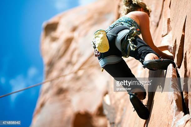 若い女性のクライミング、砂岩の崖ユタ州モアブの近く