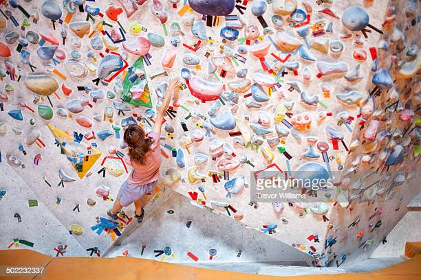A young woman climbing at abouldering gym