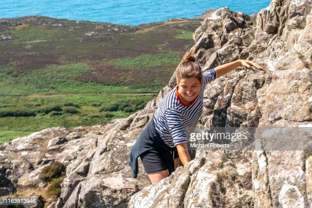 young woman climbing carn llidi at whitesands near st davids in the pembrokeshire coast national park - st davids day stock pictures, royalty-free photos & images