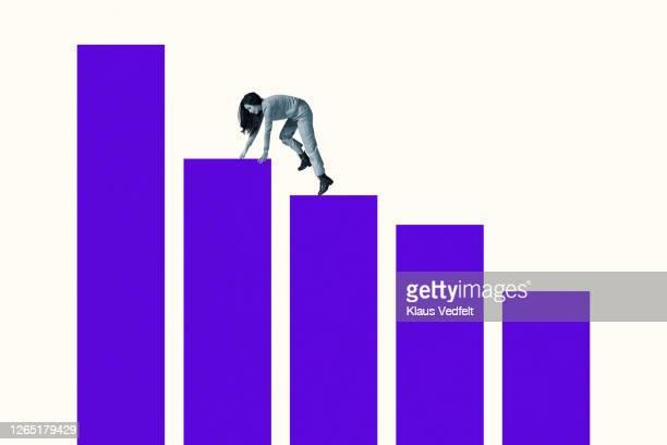 young woman climbing on blue bar graphs - balkendiagramm stock-fotos und bilder