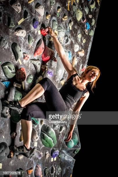 young woman climbing on bouldering wall in gym - free climbing stock pictures, royalty-free photos & images