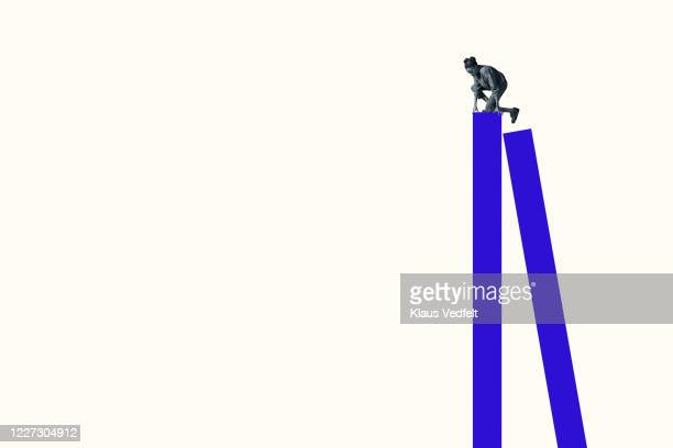 young woman climbing on tall blue bar graph - mountaineering stock pictures, royalty-free photos & images
