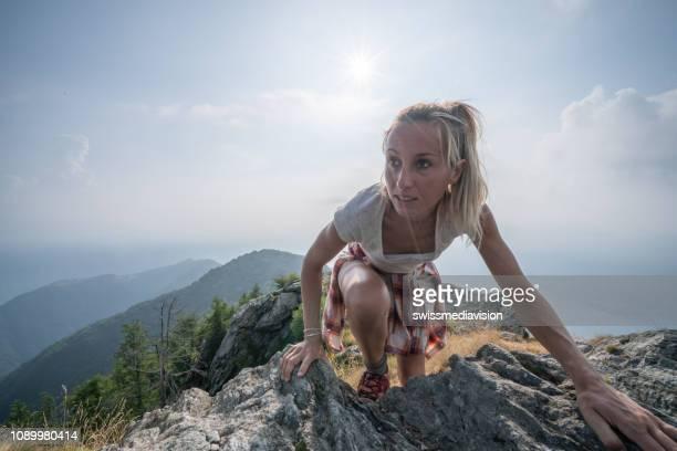 junge frau klettern fels am bergweg. menschen-outdoor-aktivitäten-konzept schuss in der schweiz - hoch position stock-fotos und bilder