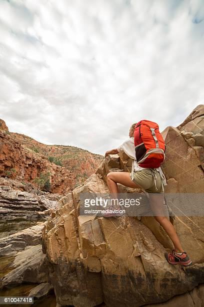 Young woman climbing rocks