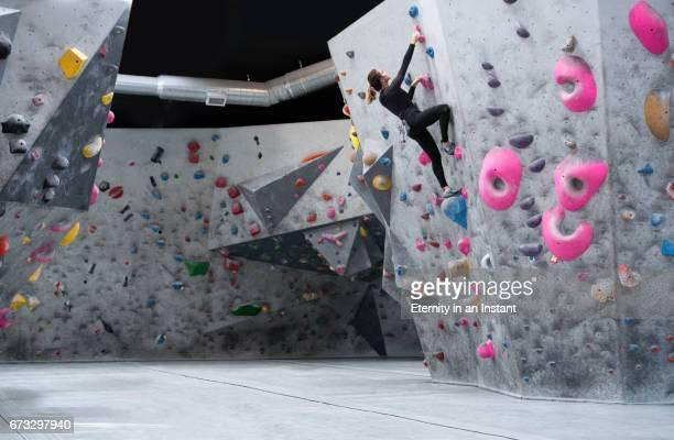 young woman climbing up a climbing wall - クライミングウォール ストックフォトと画像