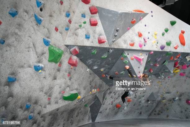 Young woman climbing up a wall