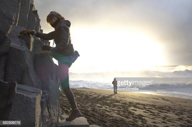Young woman climbs rocks above ocean surf
