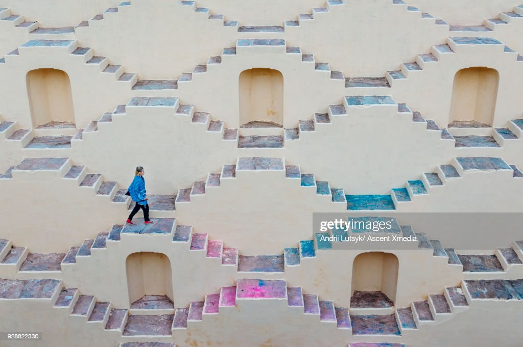 Young woman climbs staircase maze : Stock Photo