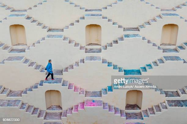 young woman climbs staircase maze - stepwell stock photos and pictures