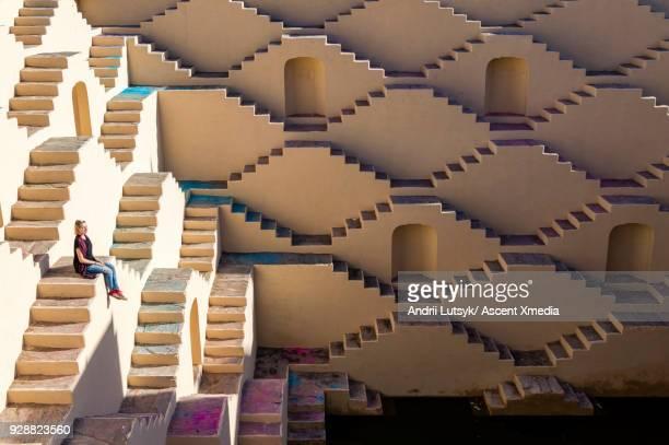 Young woman climbs staircase maze