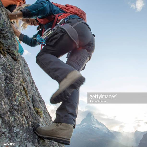 young woman climbs steep rock wall on belay - pinnacle peak stock pictures, royalty-free photos & images